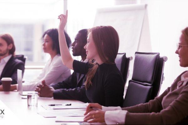 Reunião de comunicação interna em empresa em que uma mulher está levantando a mão para pedir a fala.