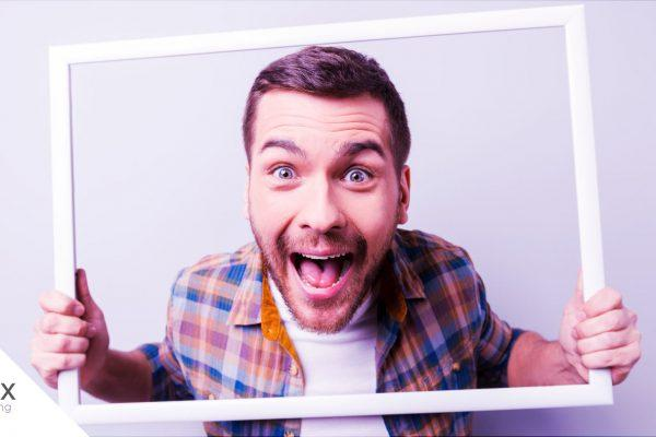 homem jovem colocando uma moldura de quadro em frente a seu rosto representando uma buyer persona